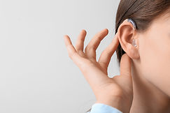Young woman with hearing aid on light ba