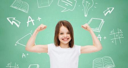 Eine Grundschülerin steht vor einer Tafel und zeigt ihre innere logische Stärke indem sie ihre Armmuskeln zeigt
