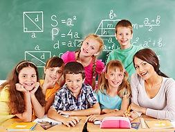 Nachhilfelehrerin mit einer Gruppe von Grundschulkindern vor Tafel gucken fröhlich in die Kamera