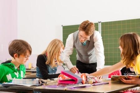 Der Englisch Nachhilfelehrer zeigt der Schülerin ihren Lernerfolg und begeistert dadurch die Schülerin der Realschule und den Schüler des Gymnasium
