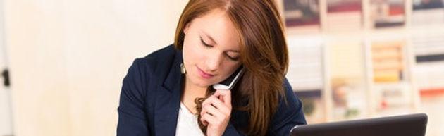 Eine Büroassistentin macht gerade telefonisch ein Anmeldegespräch mit einer Mutter aus.