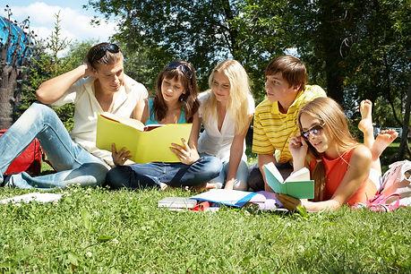 Die Schüler der Ferienkurse sitzen mit ihrem Schulmaterial auf einer Wiese und lernen mit Ihrem Nachhilfelehrer der Nachhilfe Notensprung