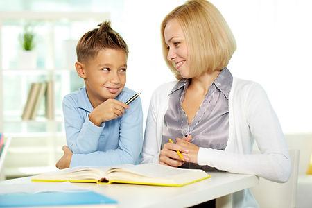 Ein Grundschüler bespricht mit seiner Nachhilfelehrerin seine gelösten Hausaufgaben