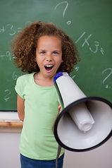 Eine Grundschülerin schreit ins Megafon wie die richtige Lösung in Mathematik ist