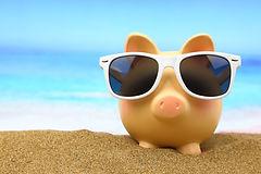 Das Bürosparschwein von der Nachhilfe Notensprung Baesweiler liegt im Sand in der Sonne