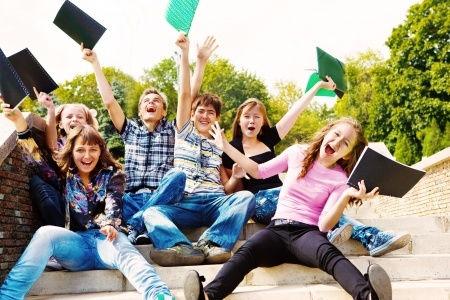 Hier sitzen die Schüler der Nachprüfungskurse mit ihren bestandenen Prüfungen auf einer Treppe und freuen sich auf die bestandene Nachprüfung