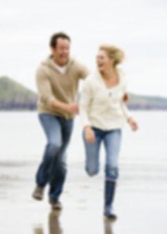 healthy couple running on beach