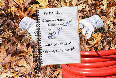 Gutter Cleaning in Freehold, To do list, work gloves, and a hose sit ongrund covered in leaves
