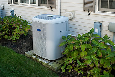 air conditioner repair in Spring Lake, Outdoor condenser shown on well manicured lawn with appropriately trimmed bushes