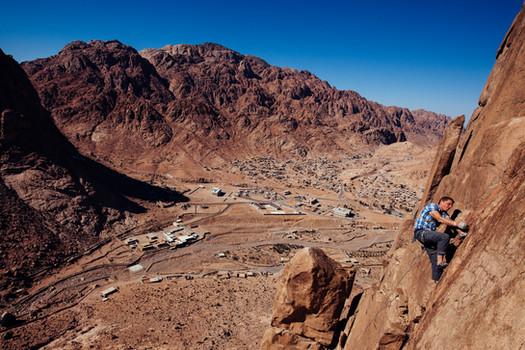 Dave Lucas climbing above St. Katherine's village in the Sinai Desert. - Egypt