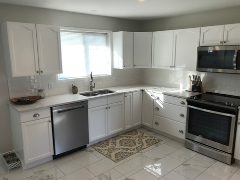 This remodel included painting existing cupboards, porcelain tile, appliances, and a wall removed for an open concept, with a beautiful support beam.