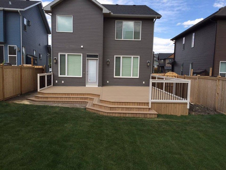Custom deck on helico piles. 2x8 structure with wrap around stairs. Stained cedar decking with grey stained posts and handrail.