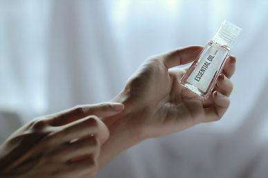 "Hand holding bottle labeled ""Hand sanitizer"""