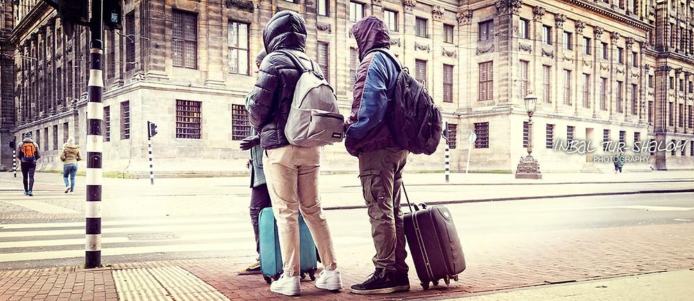 תיירים עם מעילים ומזוודות מאחורי ארמון המלוכה שבכיכר דאם באמסטרדם