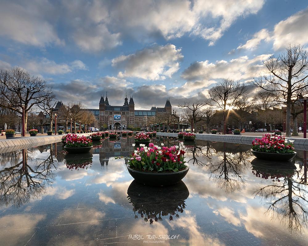 זריחה והשתקפות עננים בבריכה בכיכר המוזיאונים באמסטרדם