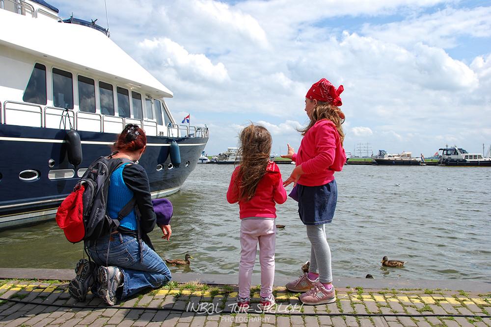 אם ובנותיה מסתכלות על ברווזים במעגן סירות Volendam