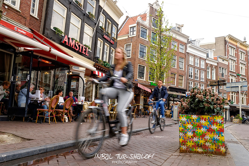 Spui Amsterdam, people riding bicycle next to a café