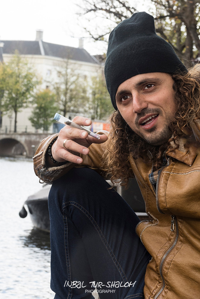 a man holding a joint sitting next to a canal in Amsterdam