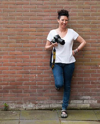 inbal Tur-Shalom standing against a red brick wall, holding a camera.