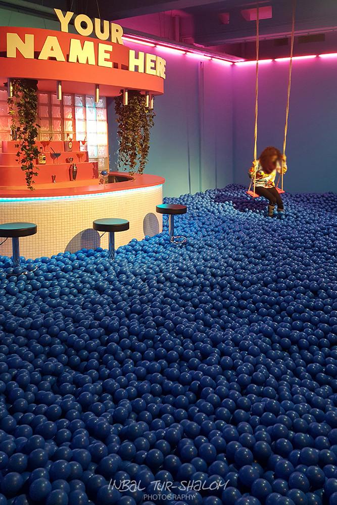 בחורה מתנדנדת על נדנדה בבריכת הכדורים הכחולים באטרקציה יוזאום