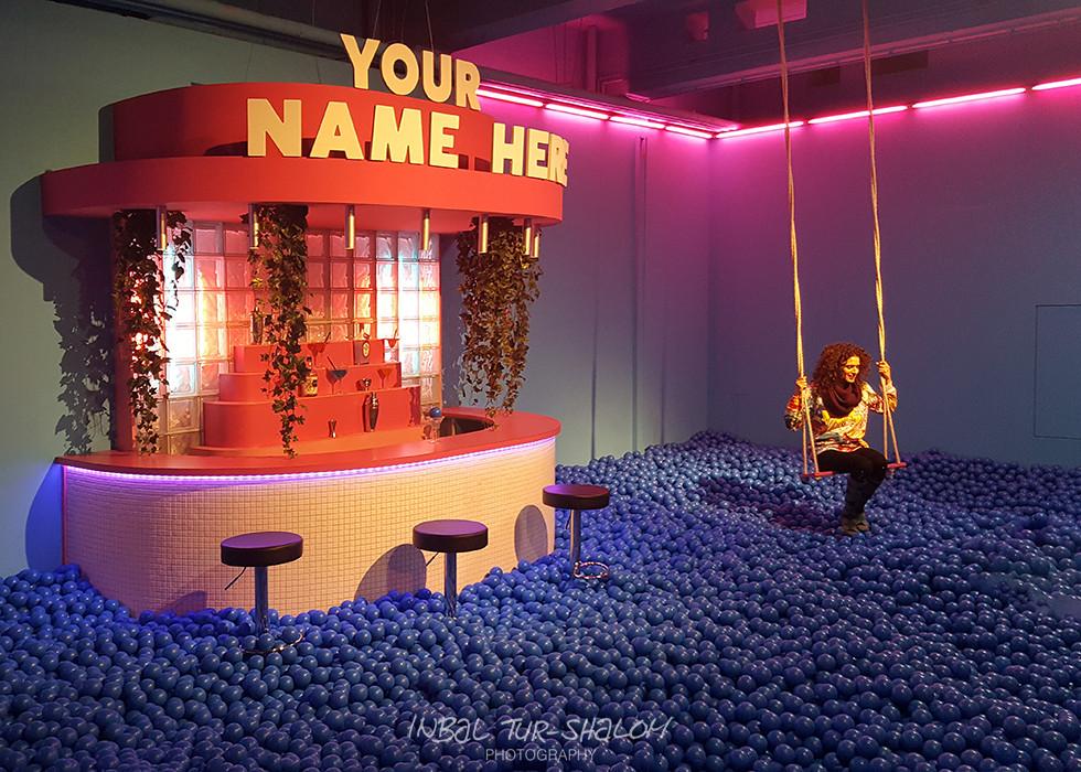 בחורה יושבת על נדנדה בתוך בריכת כדורים Youseum אמסטרדם