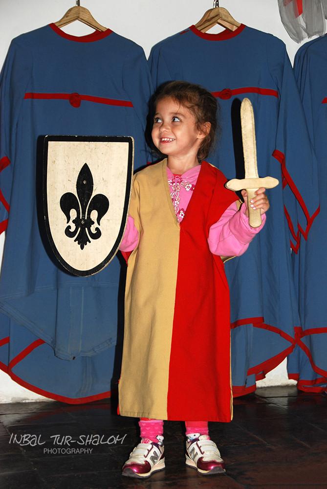 ילדה בתחפושת אביר עם חרב ומגן