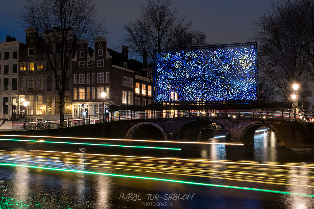 night photo boat going next to a bridge with light installation above in Amsterdam light festival December 2018