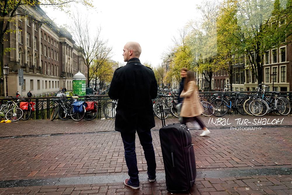 בחור עם מזוודה לידו עומד על גשר במרכז אמסטרדם מנווט עם גוגל מפותת