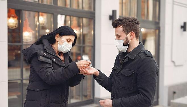 woman-putting-hand-sanitizer-on-man-s-ha
