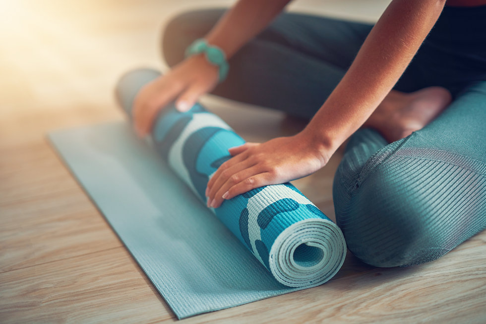 Young woman rolling yoga mat at home.jpg