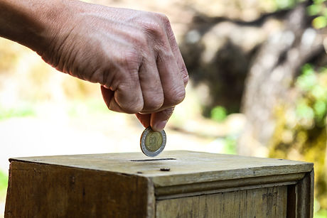 A man hand putting coin into a wooden bo