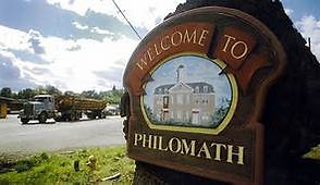 Welcome to Philomath sign with logging truck in background.