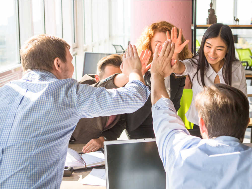 Business people happy showing teamwork and giving high-fives to show they happy about a solution that was recently implemented by a channel partner in the office. Happy people are smiling. Testimonials.