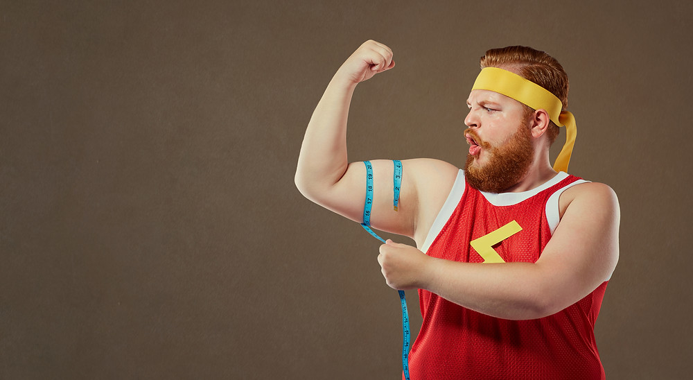 A funny fat man in sports clothes measures his arm with a centim