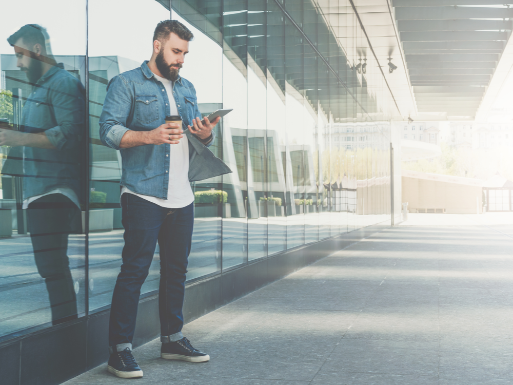 Young bearded hipster businessman stands on the city street, holds a cup of coffee, and uses a tablet computer. In the background is a modern glass building. Man working, blogging, chatting online. Social media.