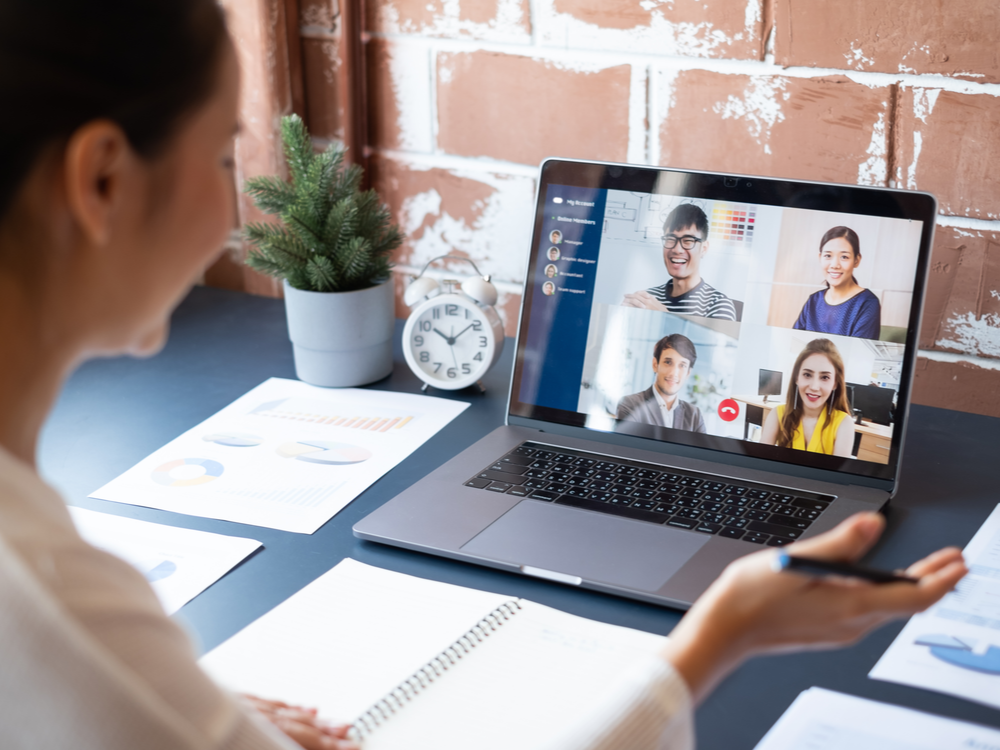 Young Asian businesswoman working at home on a virtual video conference meeting with her colleagues discussing content ideas