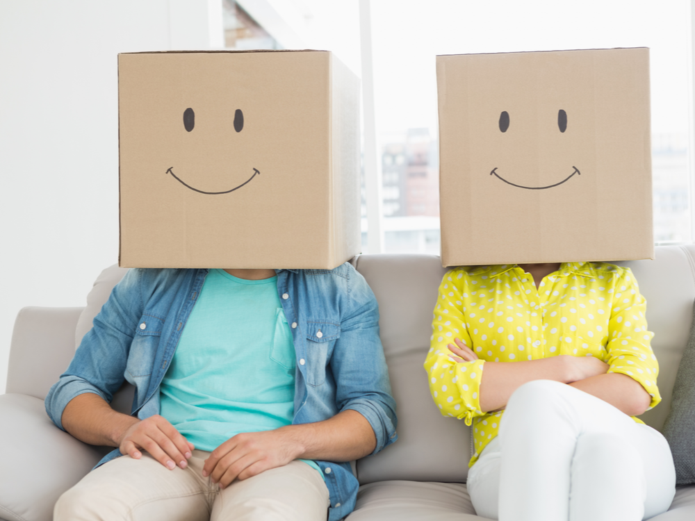 Young creative team wearing boxes on their heads in a creative office impersonating emojis.