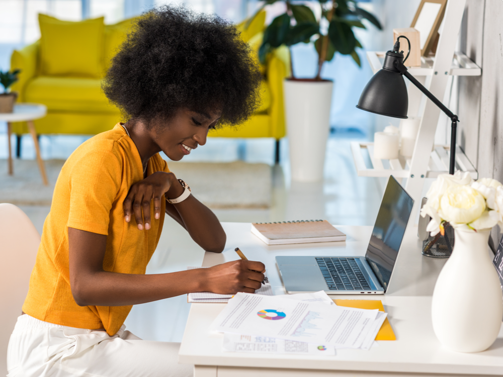 Side view of a smiling african american female working at home working on content marketing