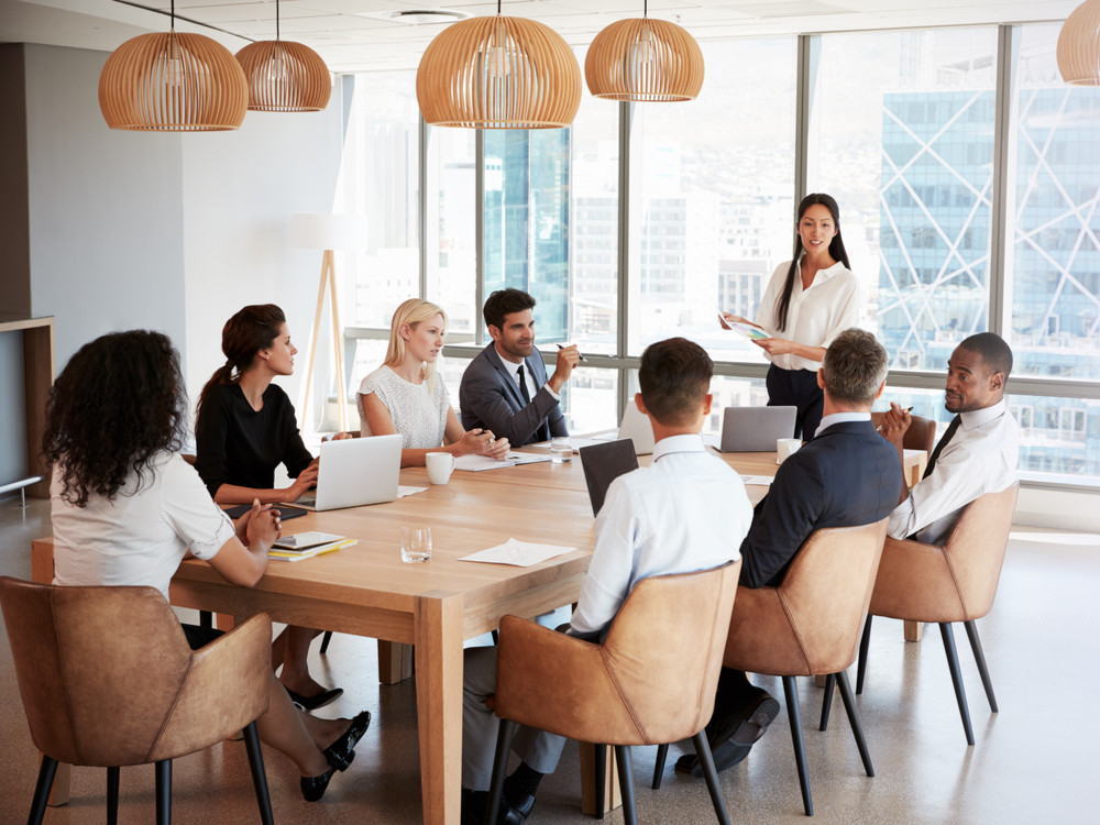 Businesswoman stands to address a meeting around the board table to discuss generating leads