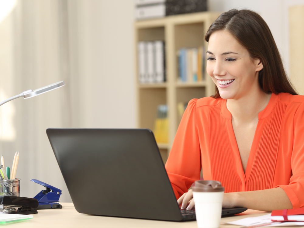 Marketing Assistant working with a laptop on her desk in an office writing a success story