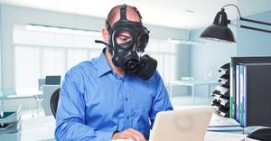 Man wearing gas mask typing on laptop