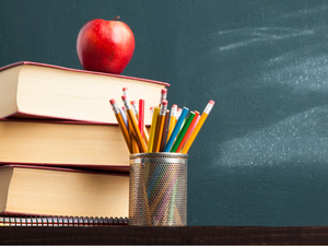 Back to school background with books and apple over blackboard | Marketing