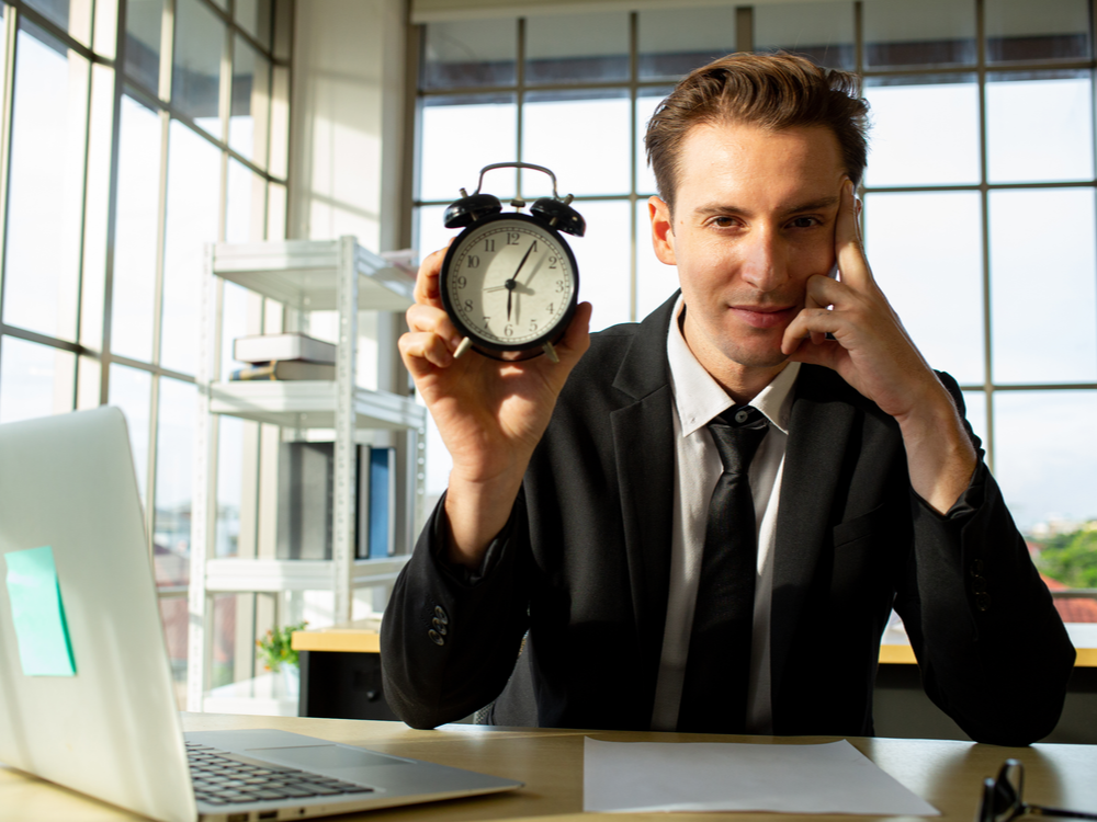 Businessman holding an alarm clock for extra sales lead and prospect research in the office. Smile face feeling good and do his job in the company.