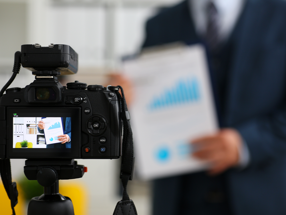 Male in a suit and tie show stats graph pad making promo video or a photo session in office camcorder to tripod closeup. Vlogger selfie sale solution or finance advisor management information