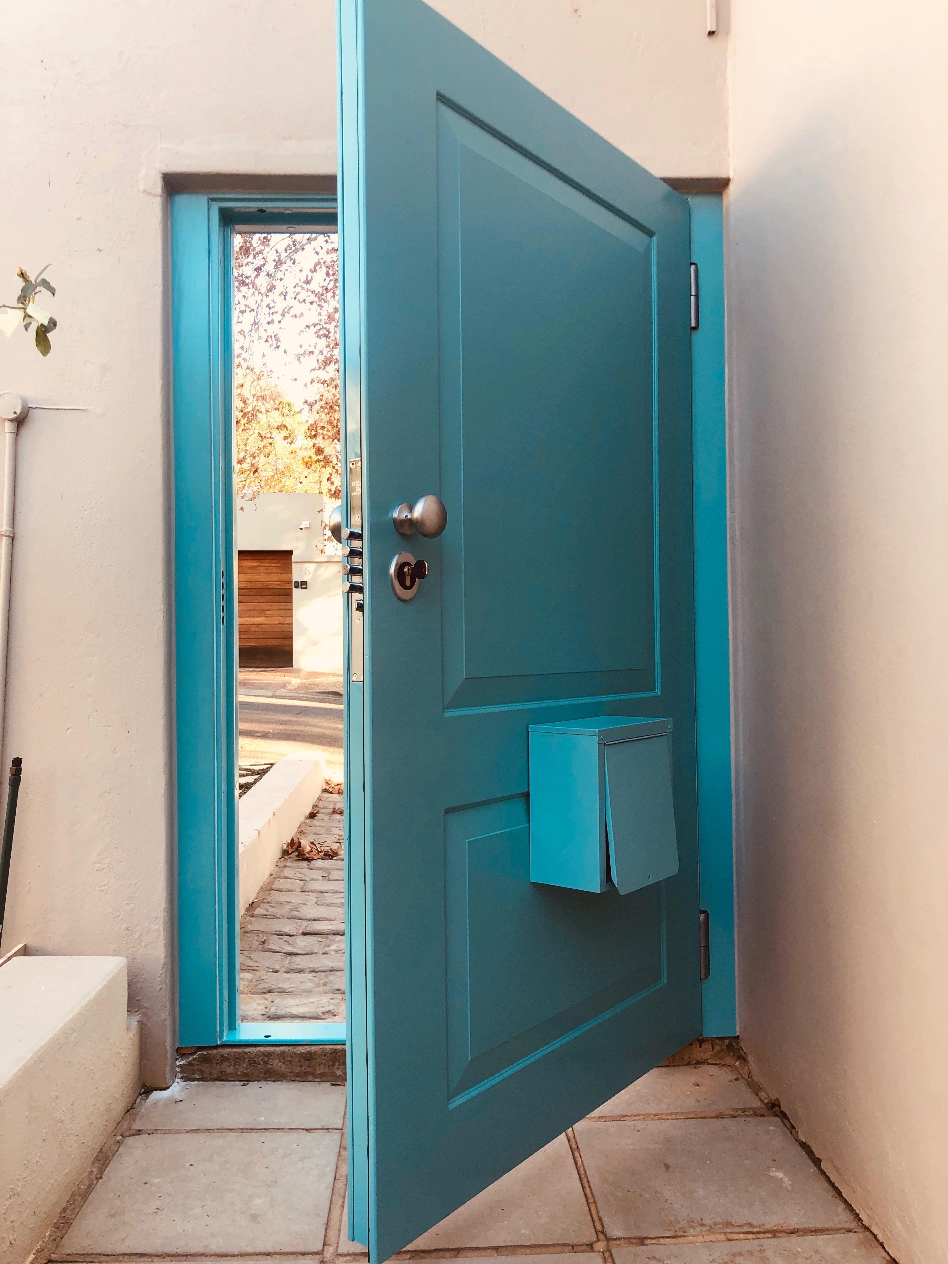 turquoise burglar door with postbox
