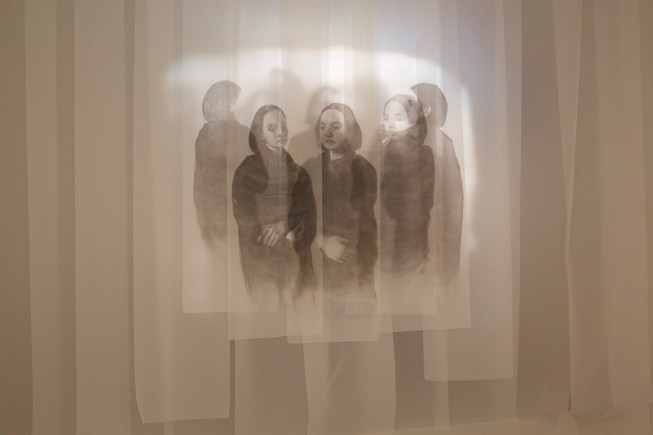 Installation shot at NCAD Graduation show, titled Gloam. 2019. Pages of varying sizes, approx. 200*50cm. Charcoal dust on tracing paper.  This large scale ongoing drawing project interrogates the link between the real and the unreal, the representation and the simulation. The work shows bodies huddled together while at the same time remaining forever separated. This idea of 'unreality' is expressed through the uncanny doubling and mirroring of the figure.