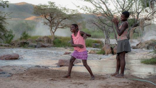 Two girls dancing at Epupa Falls