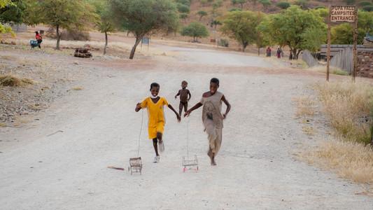 3 children running , 2 with toys