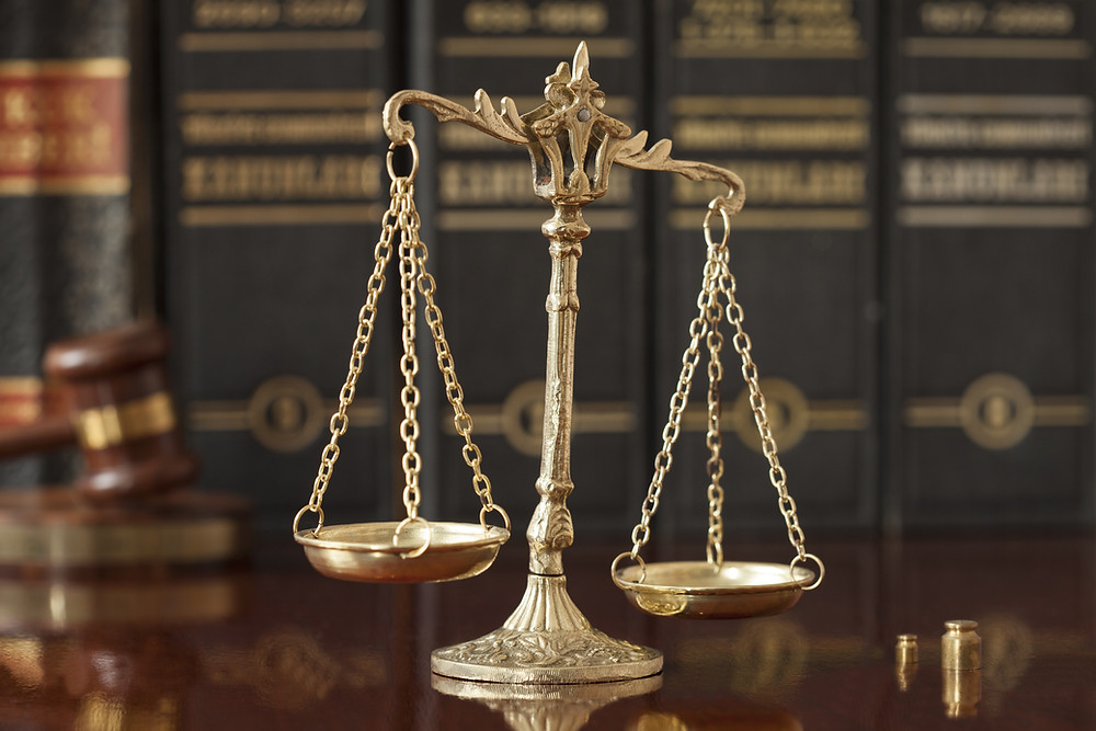 Scales of justice in front of a gavel and law books
