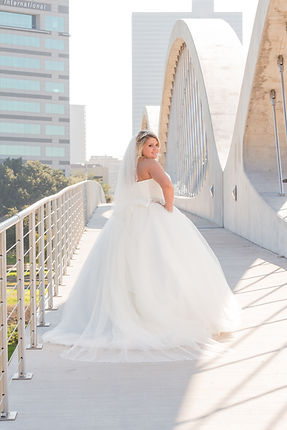 Beautiful bride, looking back, on 7th Street Bridge, with downtown skyline. Crossroads Photography.